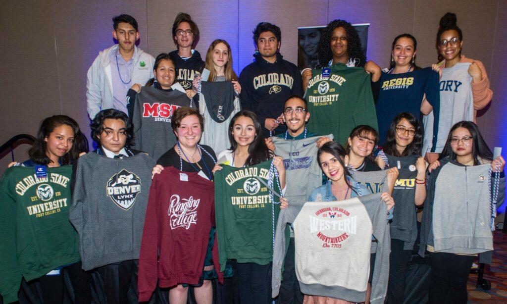 Students hold up various university sweatshirts