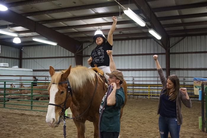 An equine therapy student on a horse raises his fist in the air.