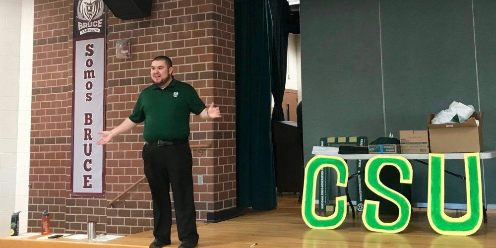 Man in a green shirt stands next to a CSU banner