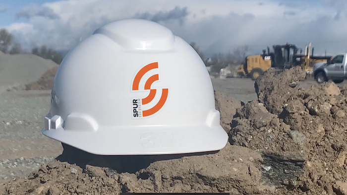 Helmet with Spur logo on construction site.