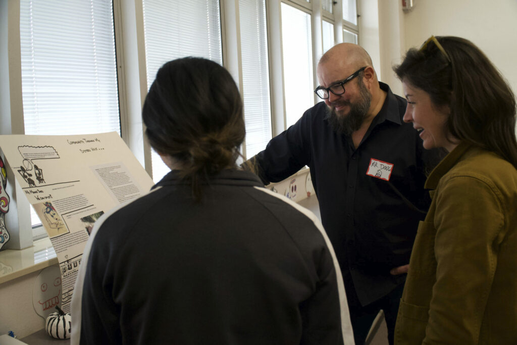 Three people look at a poster on an easel.
