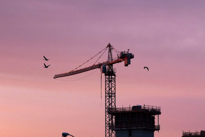 Birds and a crane are silhouetted against the sunrise.