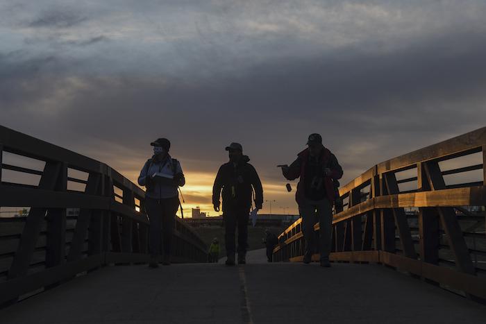 Three people on a bridge silhouetted against the sunrise