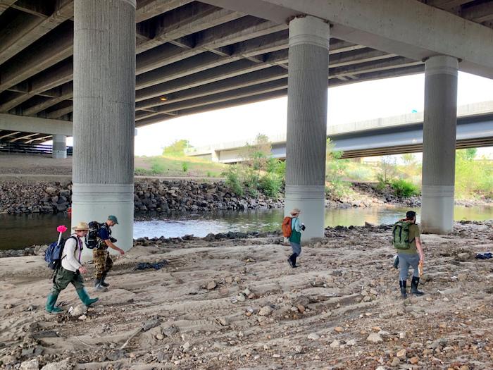 Five people walk underneath a viaduct near a river