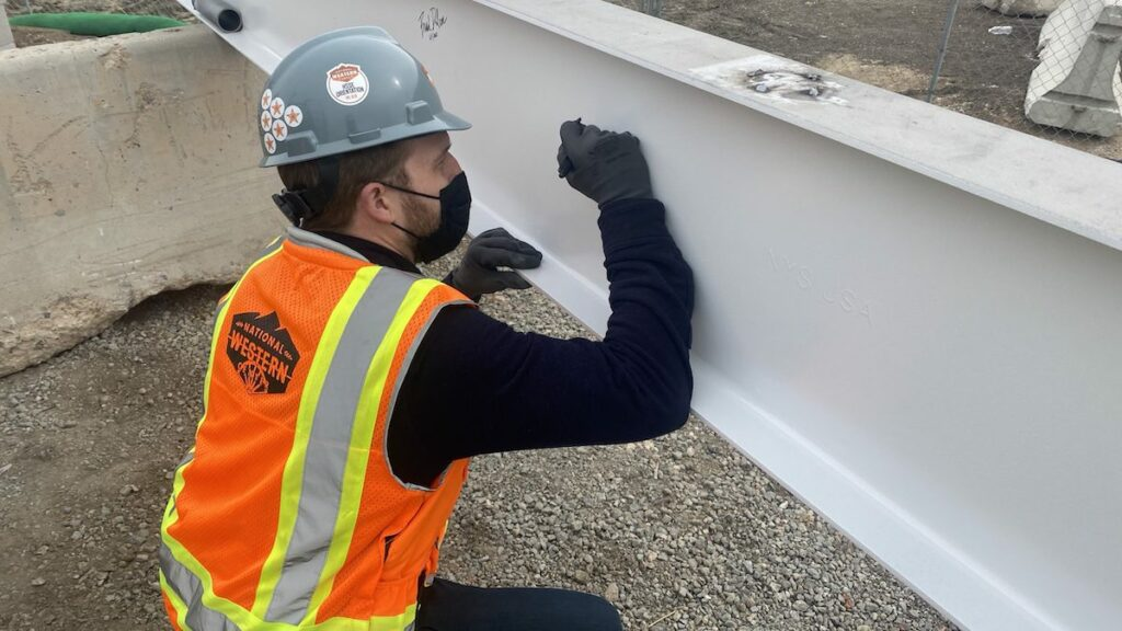 Person in a hard hat and orange vest signs a white steel beam.